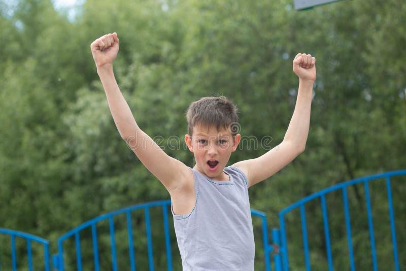 Ein Jugendlicher in einem T-Shirt und in den kurzen Hosen feiert den Sieg lizenzfreie stockfotografie
