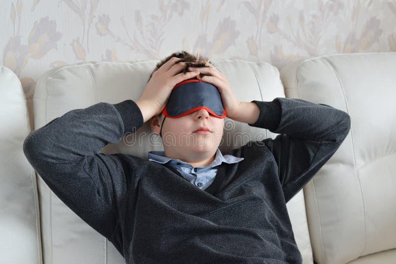 Ein Jugendlicher mit Kopfschmerzen in der Maske für Schlaf lizenzfreie stockfotos