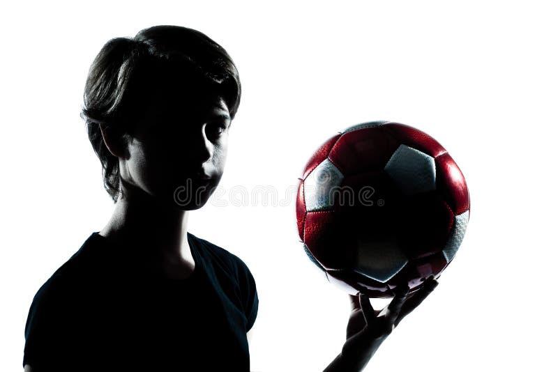 Ein Jugendlichjungen-Mädchenschattenbild, welches das Zeigen von Fußball footba hält lizenzfreies stockfoto