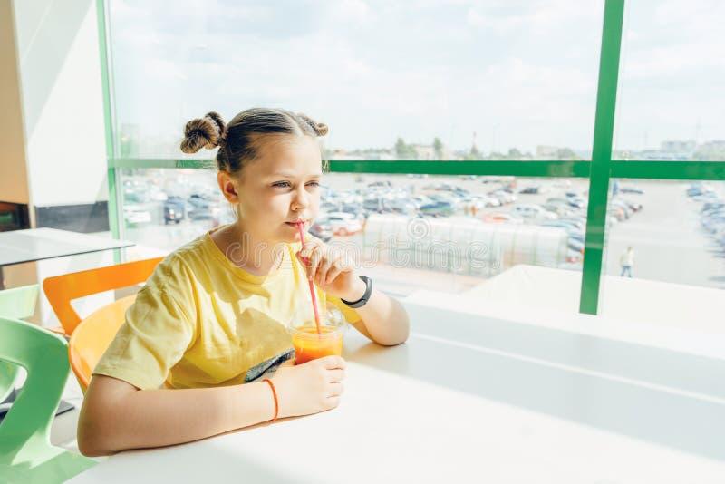 Ein Jugendlichmädchen sitzt in einem Café einen Karotte Smoothie trinkend lizenzfreies stockfoto