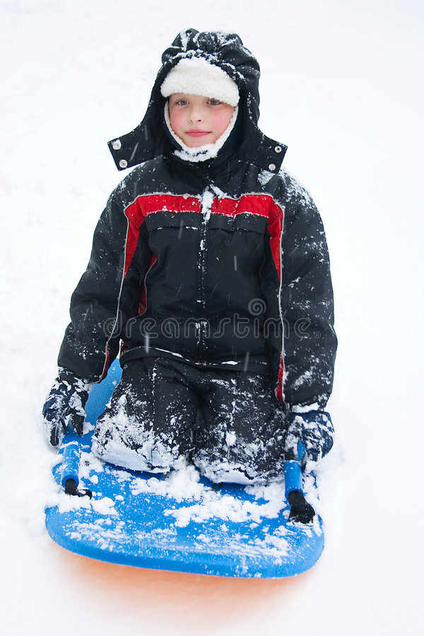 Ein Junge auf einem Schlitten stockfotografie