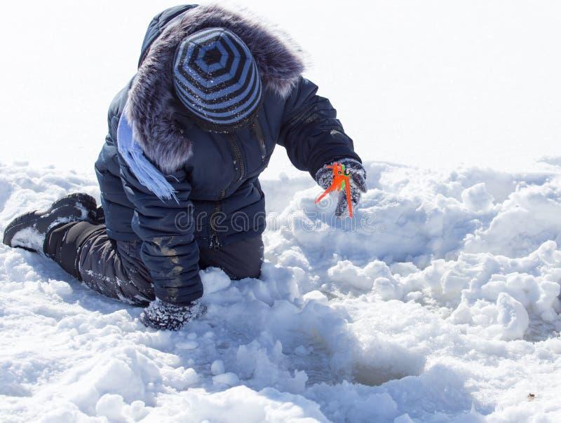 Ein Junge auf Eis fischt im Winter stockfoto