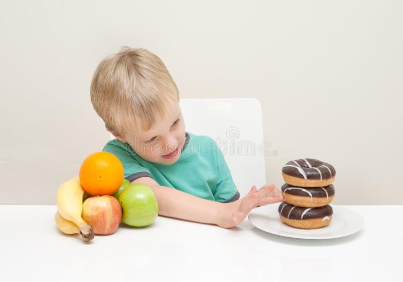 Ein Junge betrachtet, ob er einen ungesunden Donut isst lizenzfreies stockfoto