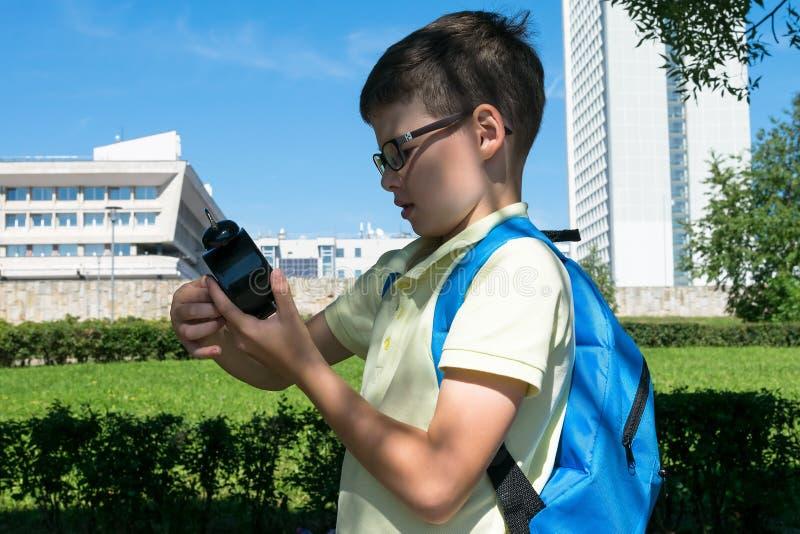 Ein Junge in den Gläsern mit einem Rucksack auf seinen hinteren Blicken auf seine Uhr bevor dem Gehen zu schulen lizenzfreies stockfoto