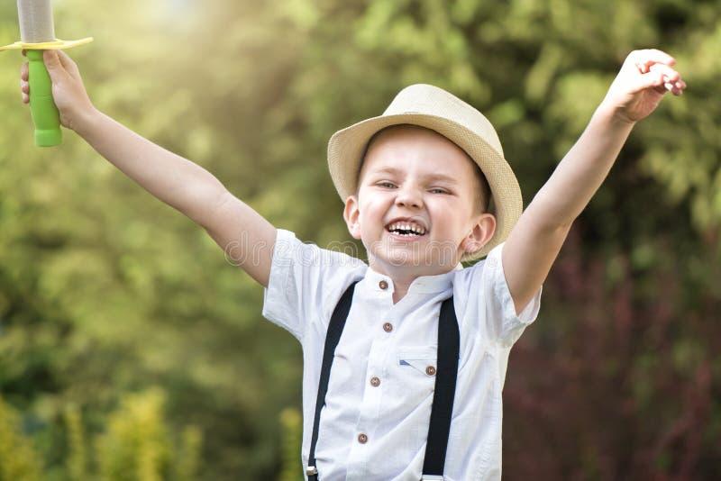 Ein Junge in den Wegen und in den Spielen eines Strohhutes im Park lizenzfreies stockfoto