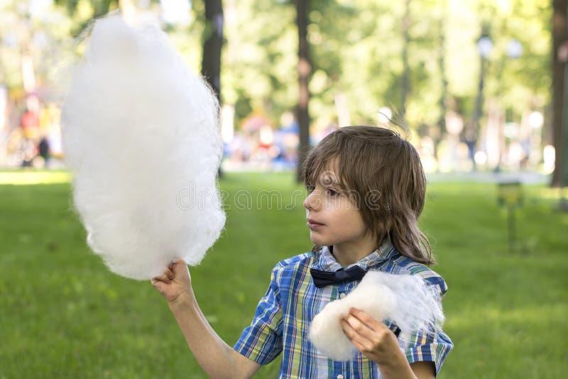 Ein Junge, der blaues Hemd mit einer Fliege tr?gt, isst Zuckerwatte im Park gegen den Hintergrund eines Rasens stockbilder