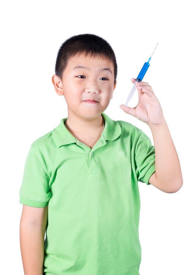 Ein Junge, der das grüne T-Shirt, Spritze in seiner Hand halten trägt lizenzfreie stockfotos
