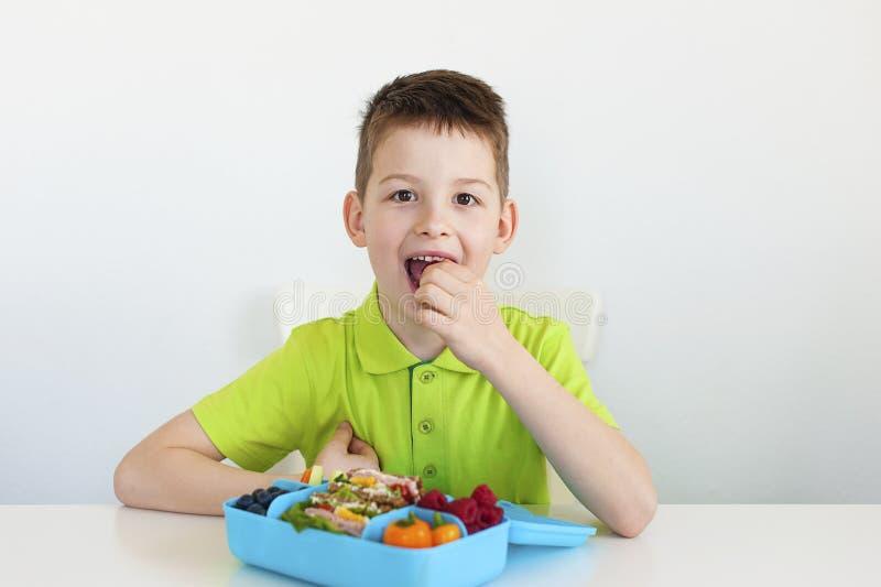 Ein Junge, der eine gesunde Schulmahlzeit isst lizenzfreies stockfoto