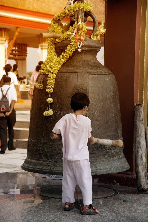 Ein Junge, der große Bell im Freien auf Hügel in Wat Sangkas Ratanakhiri-Tempel schlägt stockfotos