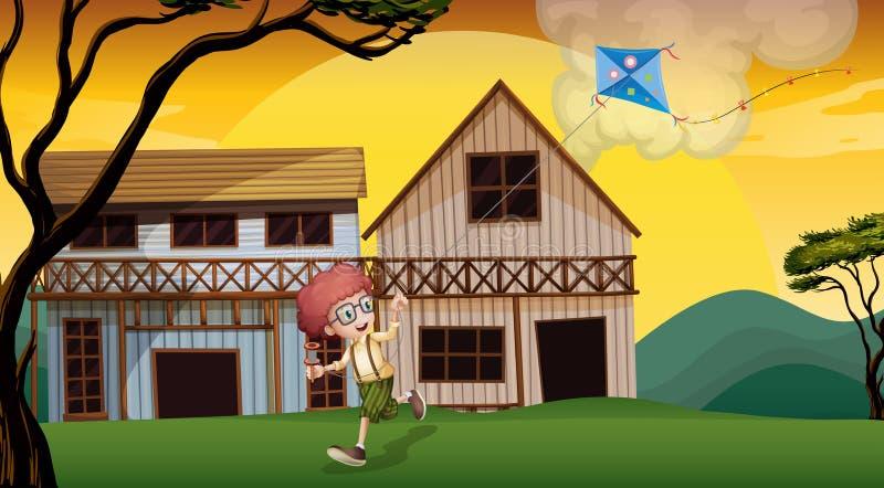 Ein Junge, der mit seinem Drachen vor den hölzernen barnhouses spielt lizenzfreie abbildung
