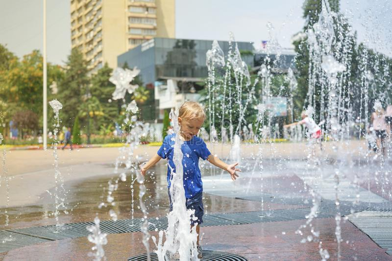 Ein Junge, der mit Wasser im Parkbrunnen spielt Hei?er Sommer lizenzfreies stockfoto