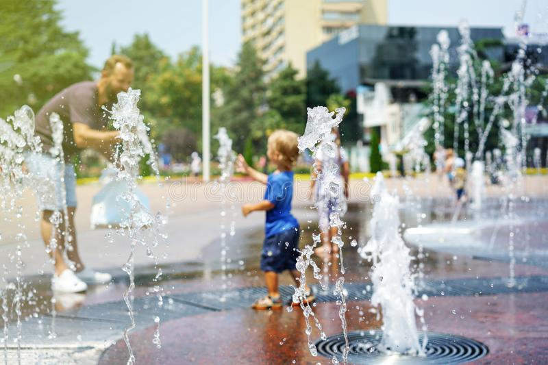 Ein Junge, der mit Wasser im Parkbrunnen spielt Hei?er Sommer stockfotografie