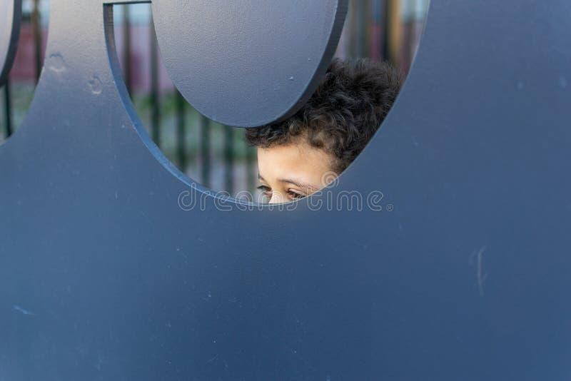 Ein Junge, der playfully heraus von hinten einen großen Metallausschnitt späht lizenzfreies stockfoto