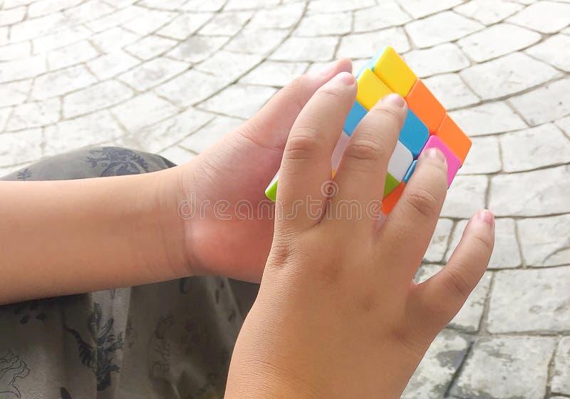 Ein Junge, der zum Lösen der 3 durch rubic Würfel 3 versucht lizenzfreie stockfotos