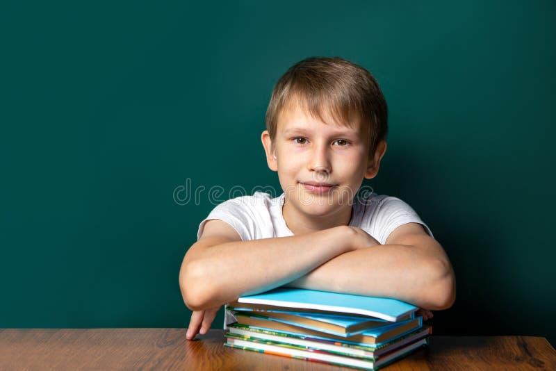 Ein Junge des kaukasischen Auftrittes auf dem Hintergrund der Schulbehörde Nahe bei ihm sind ein Stapel Notizbücher und Lehrbüche stockbild