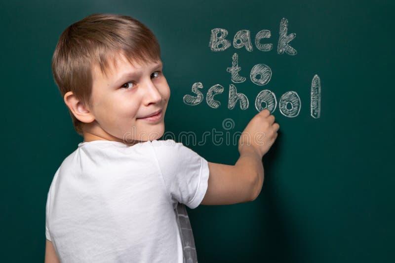 Ein Junge des kaukasischen Auftrittes schreibt zurück zu Schule auf die Tafel Betrachten der Kamera Beginn des neuen Schuljahres lizenzfreie stockfotografie