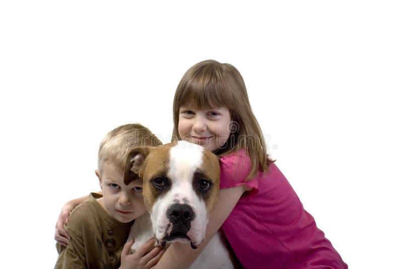 Ein Junge, ein Mädchen und ihr Hund lizenzfreie stockfotos
