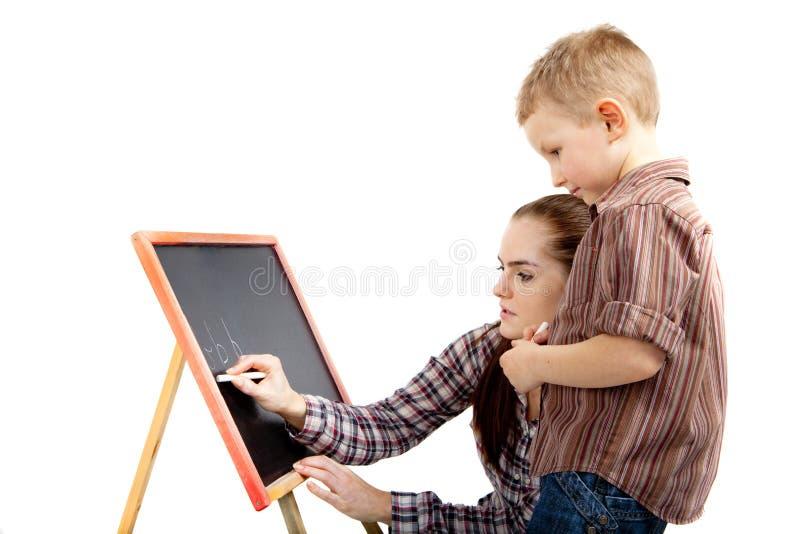 Ein Junge, eine Frau und eine Tafel. Schreiben lizenzfreies stockbild