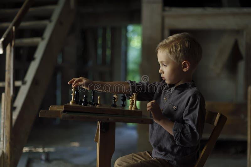 Ein Junge in einem alten Haus spielt Schach stockbild