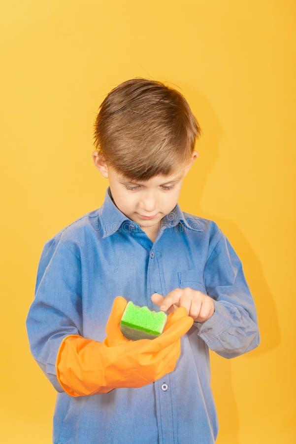Ein Junge in einem blauen Hemd und in orange Handschuhen überprüft einen grünen waschenden Schwamm lizenzfreie stockbilder