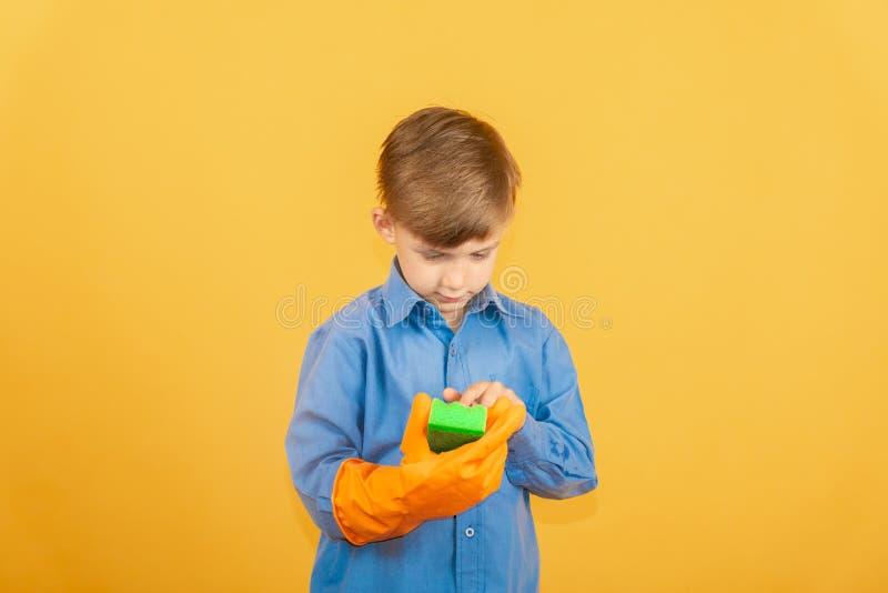 Ein Junge in einem blauen Hemd und in orange Handschuhen überprüft einen grünen waschenden Schwamm lizenzfreies stockfoto