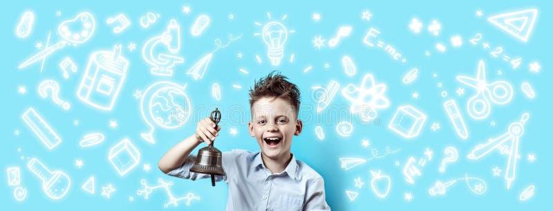 Ein Junge in einem hellen Hemd lächelt und schellt eine Glocke Herum ist es verschiedene Schulikonen auf blauem Hintergrund stockfotografie