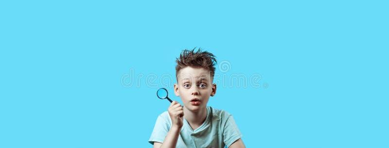 Ein Junge in einem hellen T-Shirt, das eine kleine Lupe auf blauem Hintergrund hält lizenzfreie stockfotos