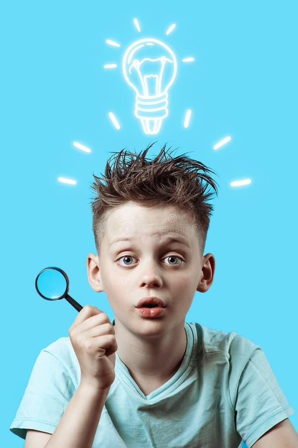 Ein Junge in einem hellen T-Shirt, das eine kleine Lupe auf blauem Hintergrund hält stockbilder