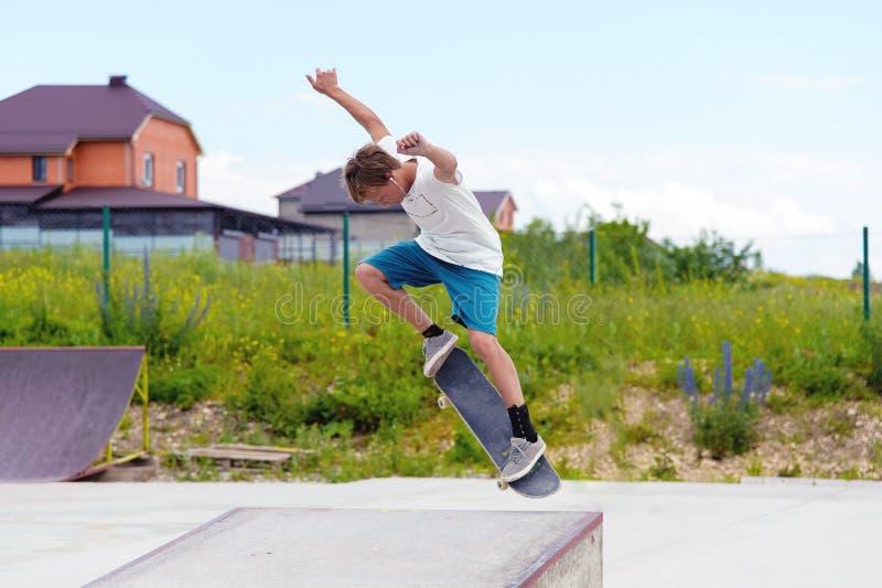 Ein Junge in einem Rochenpark, der einen Trick auf einem Skateboard tut lizenzfreie stockfotografie