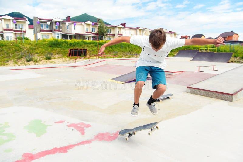 Ein Junge in einem Rochenpark, der einen Trick auf einem Skateboard tut lizenzfreie stockfotos
