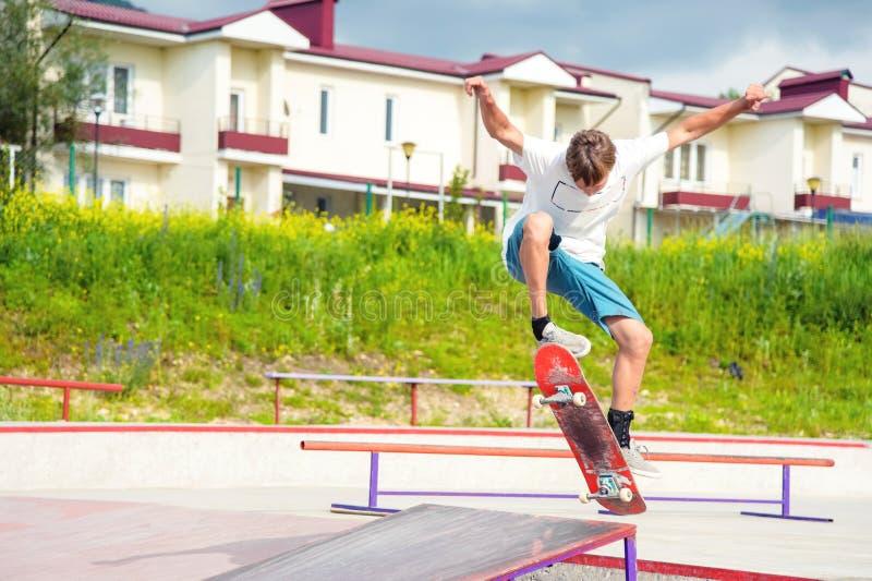 Ein Junge in einem Rochenpark, der einen Trick auf einem Skateboard tut stockbilder