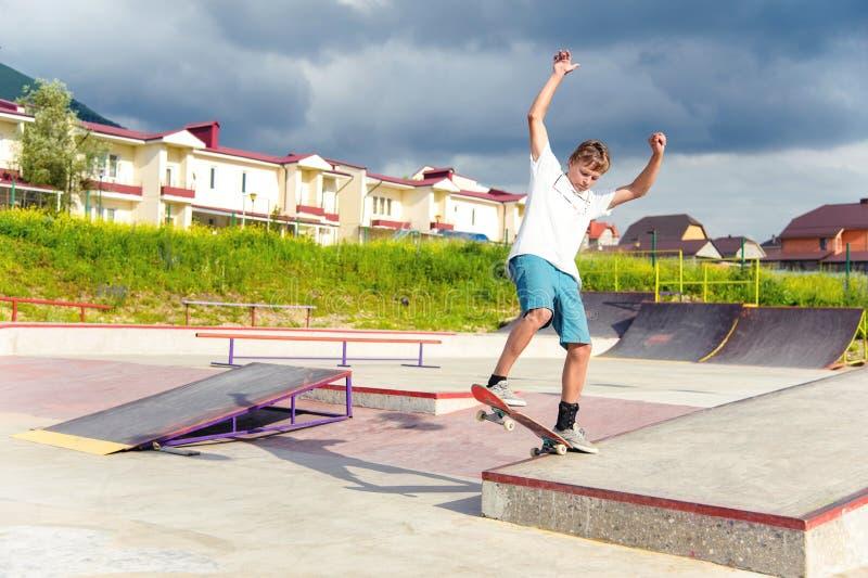 Ein Junge in einem Rochenpark, der einen Trick auf einem Skateboard tut stockbild