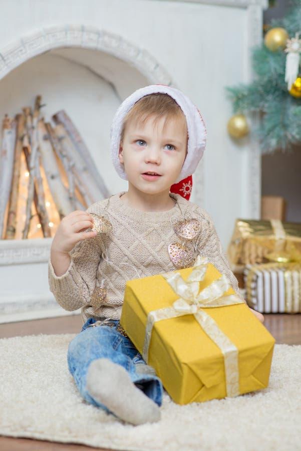 Ein Junge in einem roten Hut sitzt an einem Weihnachtsbaum mit einem Geschenk lizenzfreies stockfoto
