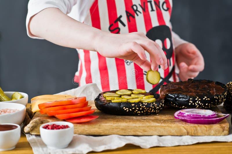 Ein Junge in einem Schutzblech kochend im K?che Burger Rezept f?r das Kochen des schwarzen cheeseberger Selbst gemachter saftiger lizenzfreie stockfotos