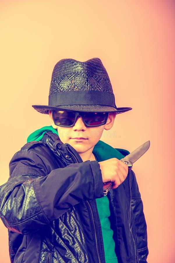 Ein Junge in einem schwarzen Hut, in den Gläsern und in einer Jacke hält ein Messer nahe der Kehle, droht mit kalten Waffen lizenzfreie stockfotos