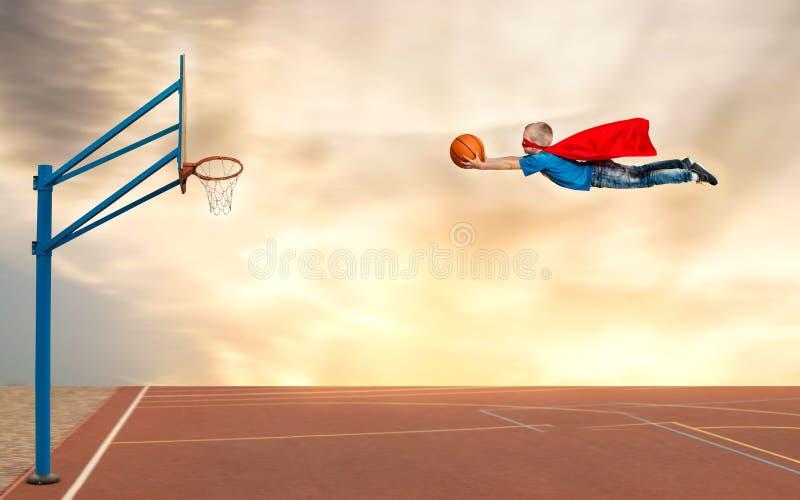 Ein Junge in einem Superheldkostüm spielt Basketball und fliegt, um den Ball in den Korb zu werfen stockbilder