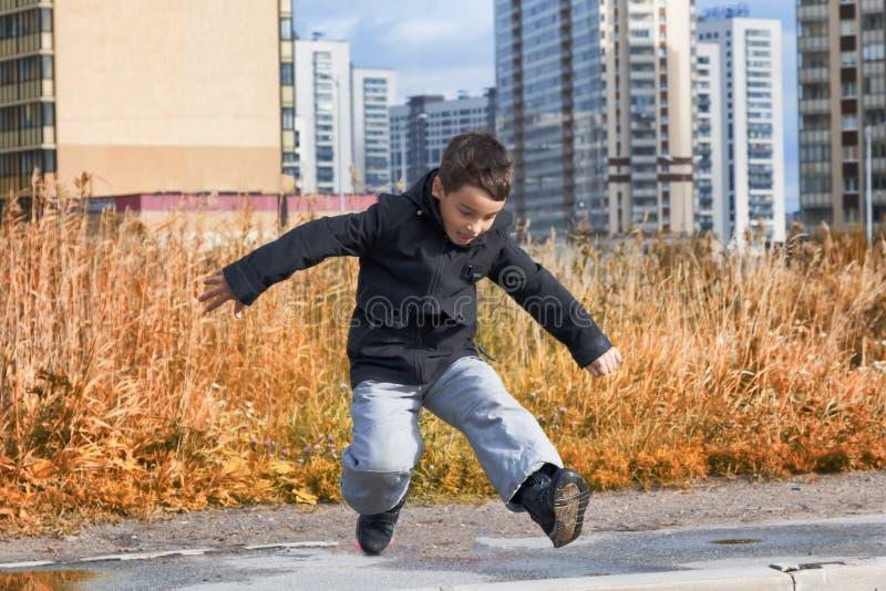 Ein Junge in einer dunklen Jacke springt eine Pfütze auf der Straße stockfoto