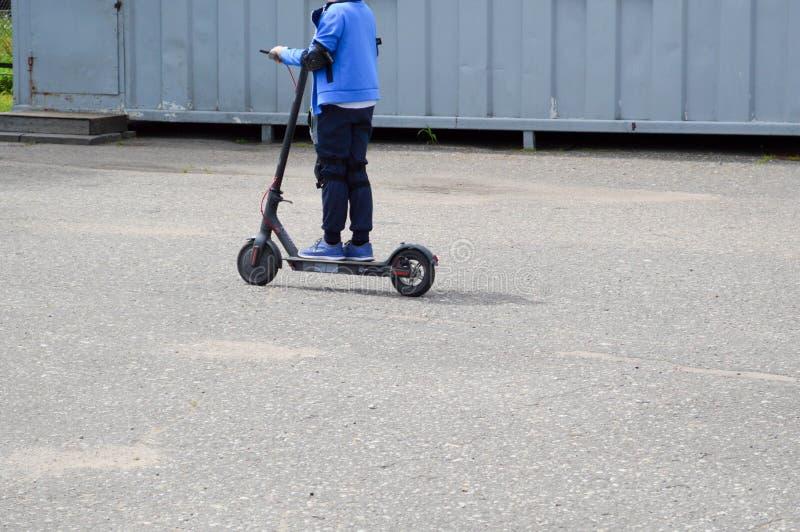 Ein Junge, Fahrten eines Mannes entlang der Parkstraße auf einem neuen modernen elektrischen Roller auf den Batterien, stehend au stockfotos