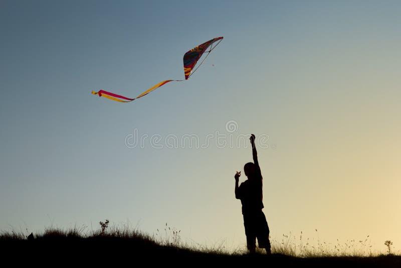 Ein Junge fliegt einen Drachen stockbild