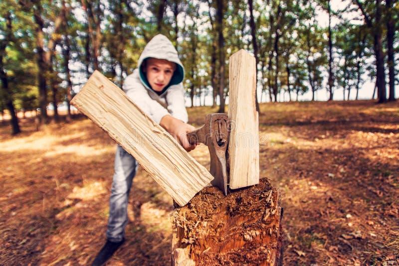 Ein Junge hat Holz mit einer Axt in einem Wald auf einem Stumpf, Weitwinkel HDR-Foto gehackt. stockfotos