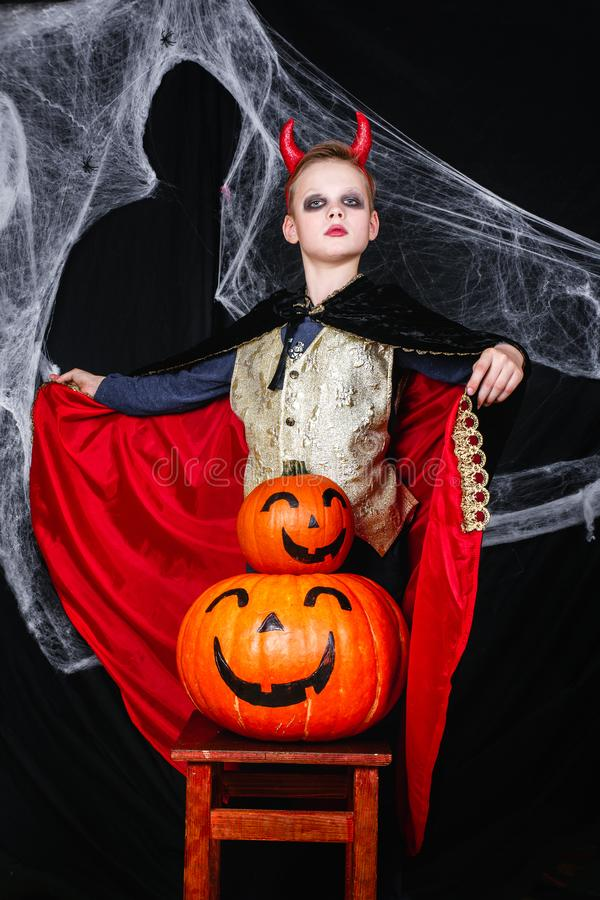 Ein Junge im Halloween-Teufelkostüm mit den Kürbisen, die Spaß auf schwarzem Hintergrund mit einem Spinnennetz haben stockbild
