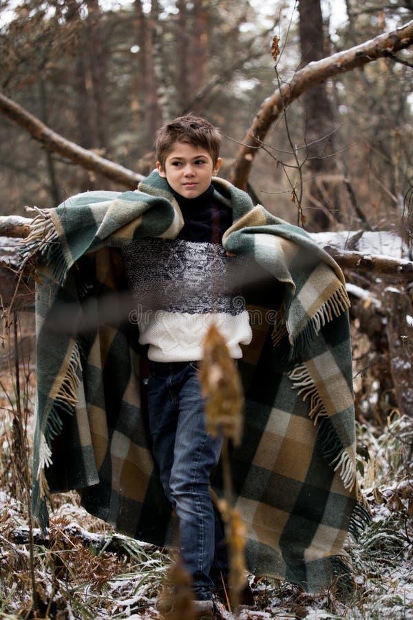 Ein Junge im Plaid geht in den Schnee im Herbstwald allein I stockbild