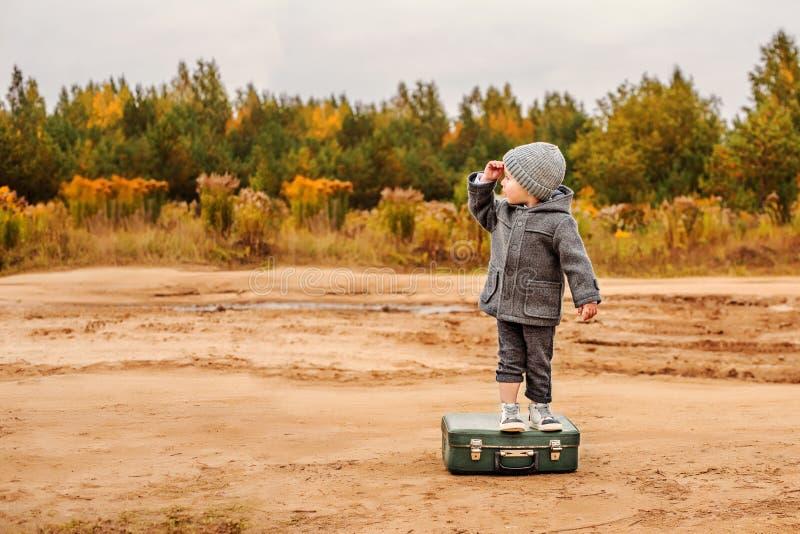 Ein Junge im Schlüpfer und in einem grauen Mantel steht auf einem alten Koffer mitten in einer sandigen Landstraße und hebt seine stockbild