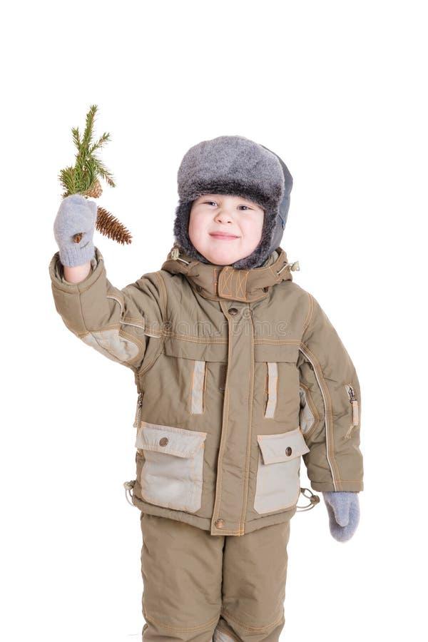 Ein Junge im Wintermantel mit einem Zweig des Pelzbaums lizenzfreies stockfoto