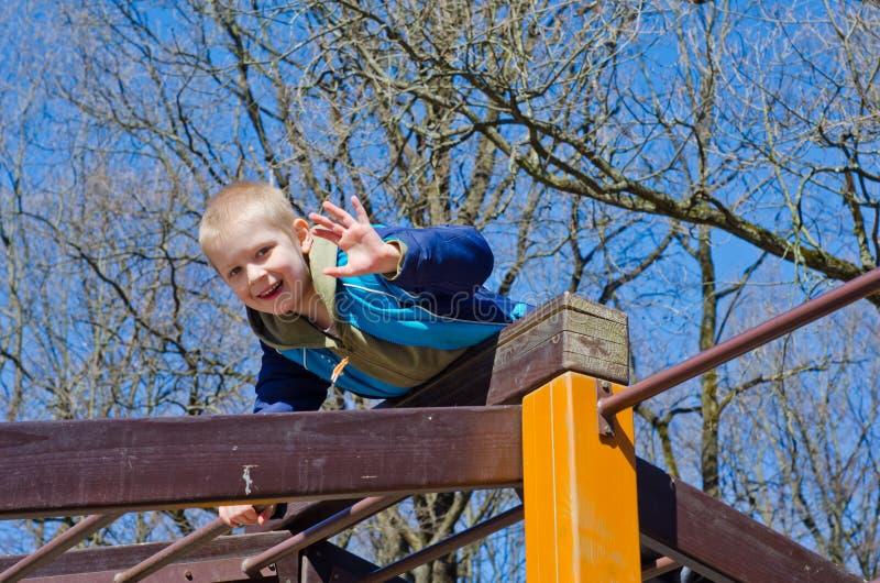 Ein Junge klettert auf Spielplatz lizenzfreie stockbilder