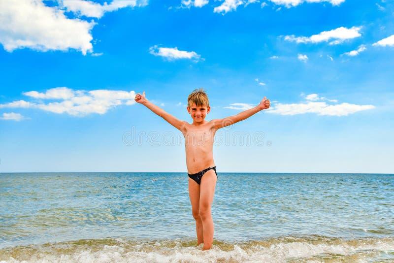 Ein Junge am Meer steht am Strand, dessen Arme sich bis an die Seiten ausstrecken stockfotografie