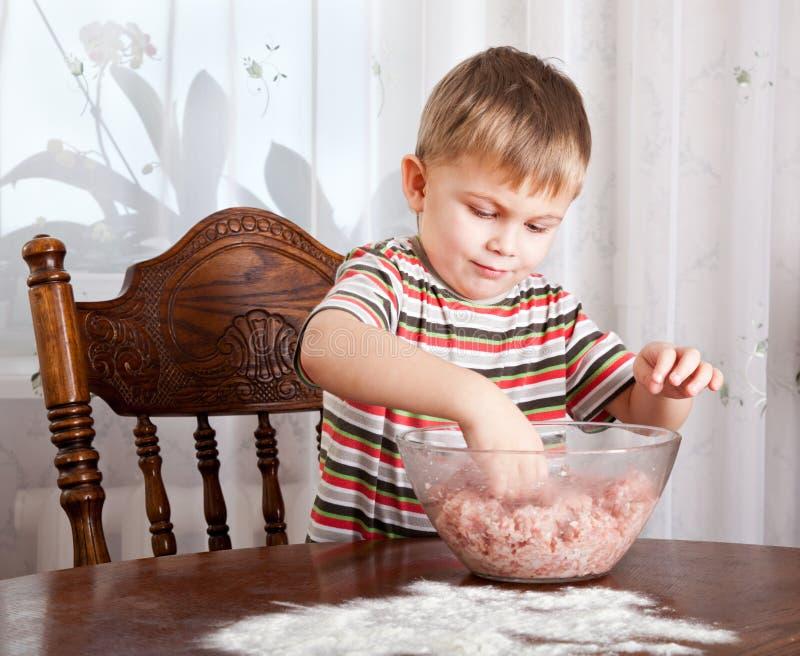Ein Junge mischt Hackfleisch in einer Schüssel stockfoto