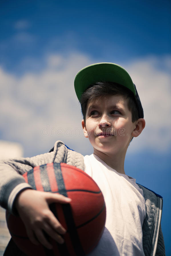 Ein Junge mit einem Basketballball auf dem Hintergrund des Himmels Das Konzept des Sports stockbilder