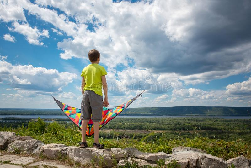 Ein Junge mit einem bunten Drachen in seinen Händen gegen den blauen Himmel mit Wolken Ein Kind in einem gelben T-Shirt und in de stockbilder