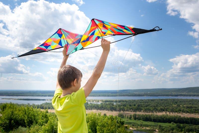 Ein Junge mit einem bunten Drachen in seinen Händen gegen den blauen Himmel mit Wolken Ein Kind in einem gelben T-Shirt und in de stockbild